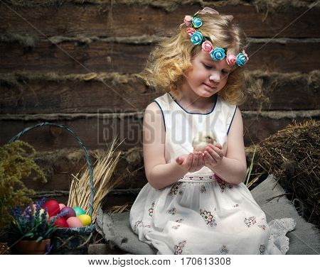 Beautiful little girl in the village in the hayloft with a newborn chick in his hands. Easter eggs in a basket. Dress wreath