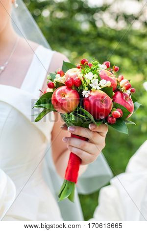 Bride holding wedding bouquet made of green leaves white flowers red apples and berries