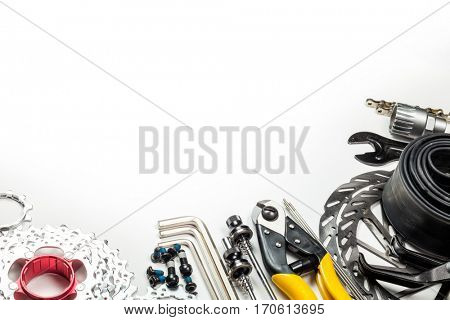 Mountain bike spares  cassette bolts chain skewers brake disk rotors levers tube sprockets and tools allen keys cable cutter on white background