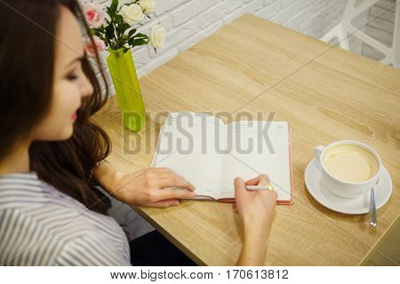 Pretty smiling woman makes entry in her diary on table. One hand writes notes and other holds skraping book. Cup of cappuccino, vase with pink and white roses stand on desk.