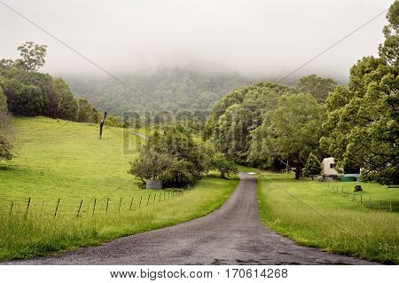 A road winds through a valley with farmland in the Gold Coast hinterland, near Canungra, on an overcast and rainy afternoon.