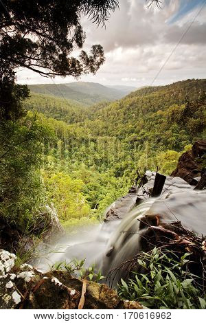 A waterfall drops off into a deep valley in Springbrook National Park, Gold Coast, Queensland, Australia.