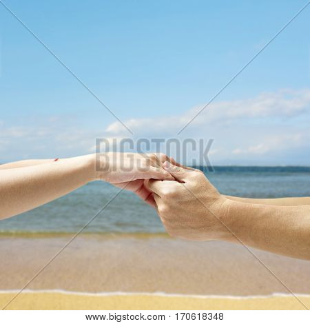 hands of a young couple held together against a sky sea and beach background.