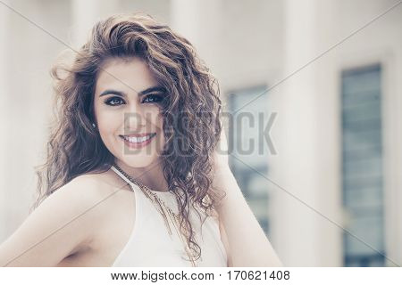 Feminine beauty. Curly hair young smiling woman. A young, smiling and attractive woman with makeup. She has long curly hair. Sensual and radiant beauty.
