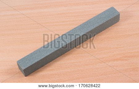 grindstone on the wooden background with the help of the bar to sharpen knife blades making them sharp