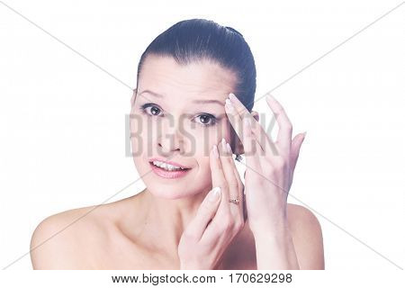 Young girl examining her face and wrinkles that can appear isola
