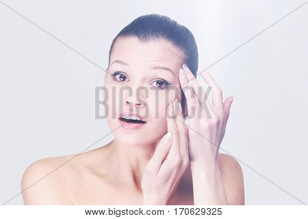 Young woman examining her face and wrinkles that can appear, iso