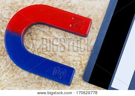 Closeup of magnet pulling credit card on fiber paper background