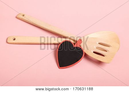 Love and Cooking concept. Wooden kitchen utensils(spade of frying pan) and black blank slate heart with space for text on pink background.