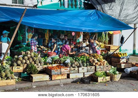 FLORES, GUATEMALA-DEC 22, 2015:  Local people selling green vegetable and fruits in Flores on Dec 22, 2015. Guatemala.