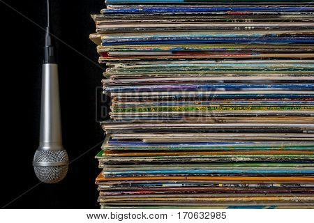 Pile of old vinyl records and microphone on a black background