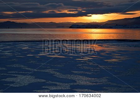 Winter landscape with ice formation process on lake at sunset combination of ice area covered with snow spots and smooth surface of water area
