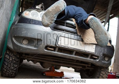 Repair of a large SUV car in a private garage cheapest feet with his hands protruding from the hood