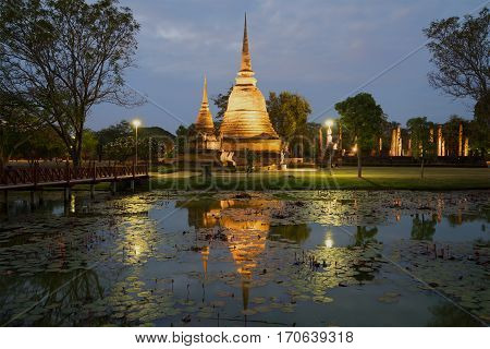 View of ruins of the ancient Buddhist temple of Wat Sa Si in evening twilight. Sukhothai, Thailand