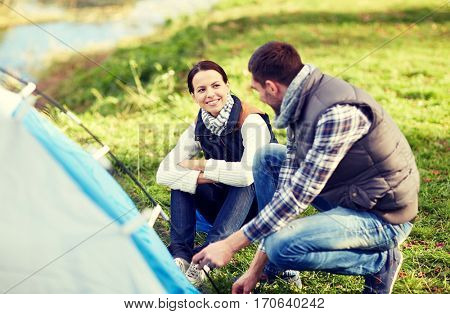 camping, travel, tourism, hike and people concept - happy couple setting up tent outdoors