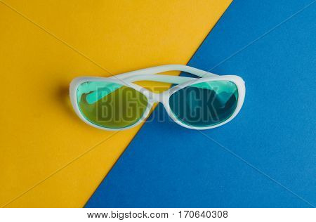 White Sunglasses On A Blue Yellow Background. Rest Concepts