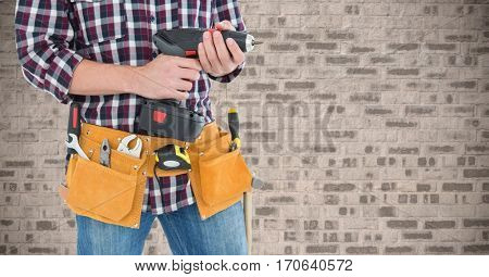 Mid section of handyman with tool belt and drill machine against brick wall