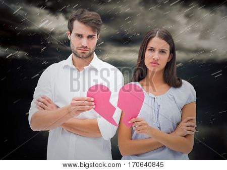 Composite image of depressed couple holding broken heart against storm clouds