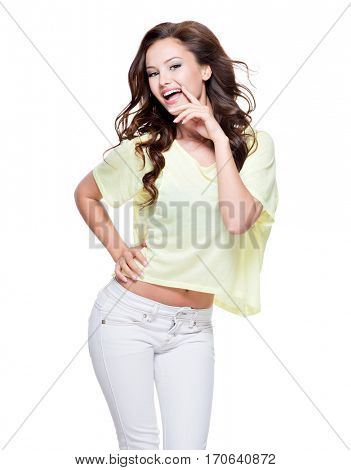 Young happy expressive woman with long brown curly hair posing over white background. Full portrait fashion model at studio.