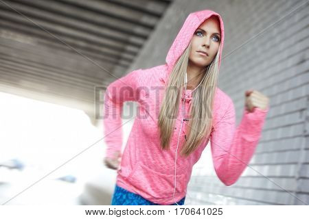 Urban life, workout in the big city. Woman wearing colorful sport dress running in a concrete gray tunnel.