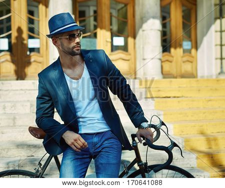 Portrait of urban hipster man in sunglasses and hat posing with bicycle in front of big city building.