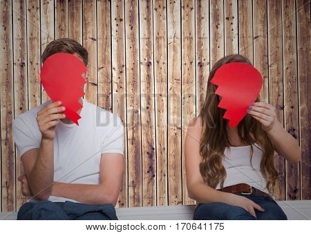Separated couple holding broken heart in front of their faces