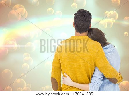 Rear view of couple embracing each other against digitally generated background