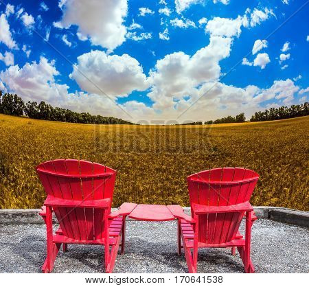 Convenient, comfortable red chairs in a wheat field. The concept of eco-tourism. Rustic vacation