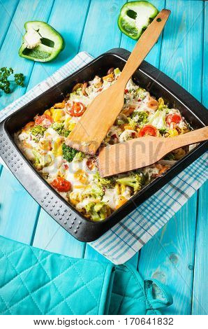 Baked pasta with broccoli and cheesy tomato sauce on blue wood background.