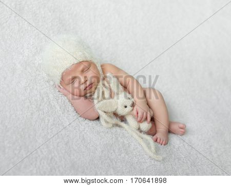 bare sleeping baby in hat with toy on white soft blanket with hand under his head