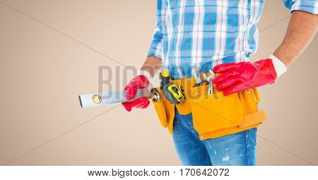 Mid section of handy man with tool belt against cream background