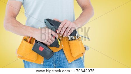 Mid-section of handy man with tool belt and drill against yellow background