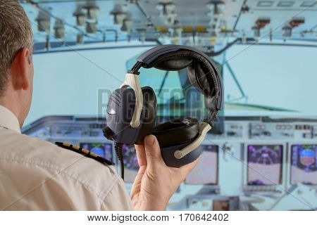 Captain holding his headphones in the cockipit of commercial airplane