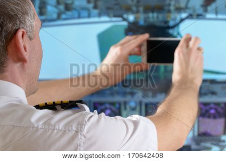 Airline pilot wearing uniform with epauletes taking pictures with smart phone in airplane cockpit