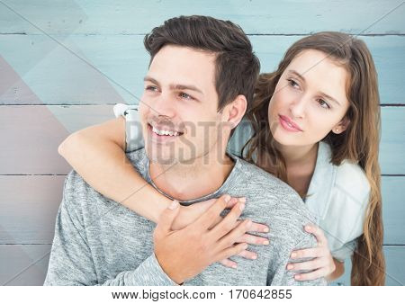 Happy couple embracing each other in front of wooden background