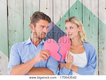 Depressed couple holding broken heart against wooden background