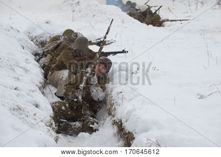 KRASNOE SELO, RUSSIA - JANUARY 15, 2017: The soviet infantryman reloads his rifle in the trenches. The reconstruction of the battle that broke the siege of Leningrad during the great Patriotic war