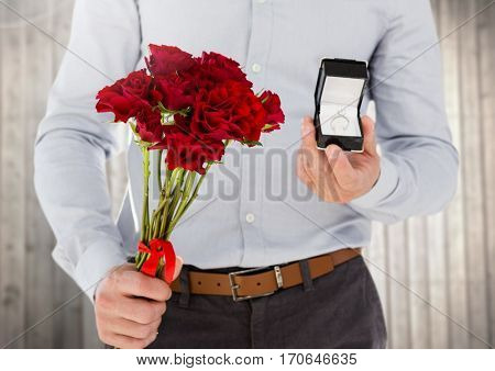 Mid-section of man holding engagement ring and flower bouquet against wooden background