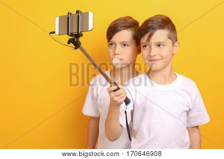 Twin brothers taking photo on yellow background