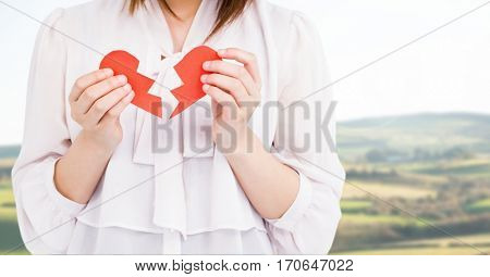 Mid-section of a woman holding a broken heart on a sunny day