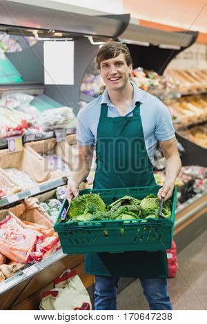 Portrait of man grocer holding a crate of vegetables on a grocery