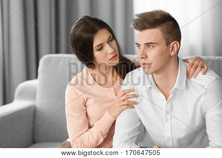Young depressed man with girlfriend at home