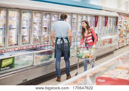 Woman talking with a man grocer on a grocery