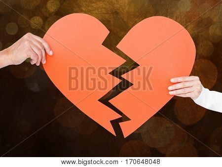 Hands of couple holding a broken heart against bokeh