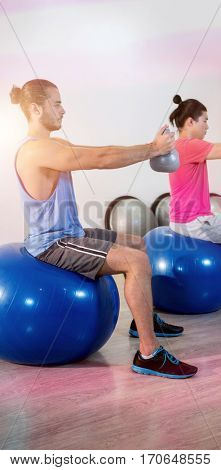 Side view of men performing stretching exercise on exercise ball in gym