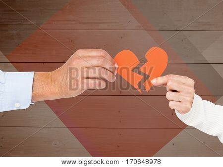 Hands of couple holding a broken heart against wooden background