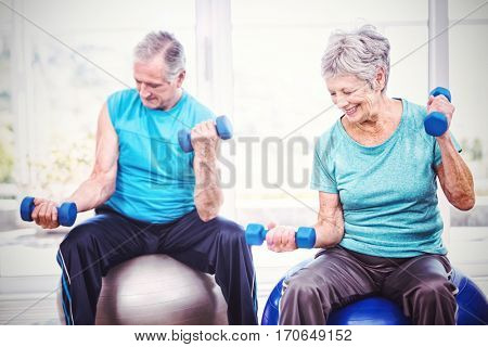Smiling senior couple holding dumbbells while sitting on exercise ball at home