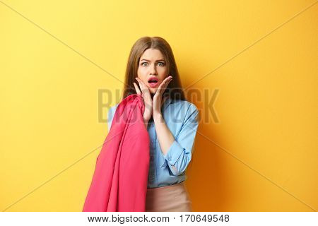 Young woman posing with jacket on yellow background