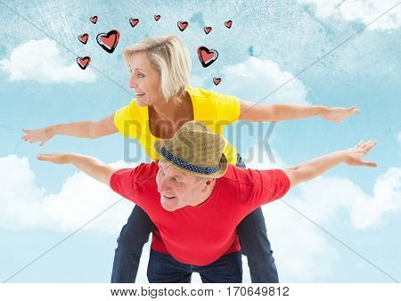Mature man giving piggy back to woman against digitally generated sky background