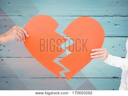 Close up of couple hands holding broken heart against wooden background